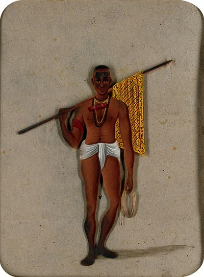 A Man Wearing a Loin Cloth Holding a Stick with a Piece of Cloth Draped around It and a Coil of Stri